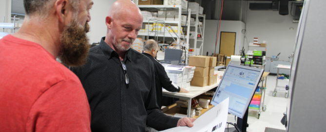 Alan Ludington in the shop looking at colors in digital printing - Artisan Colour